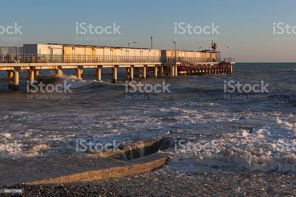 Big wave covered breakwater at the pier in resort Adler stock photo