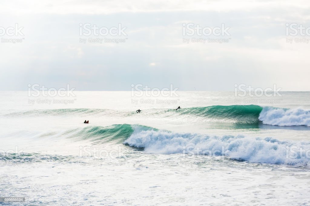 Big wave in ocean and surfers stock photo