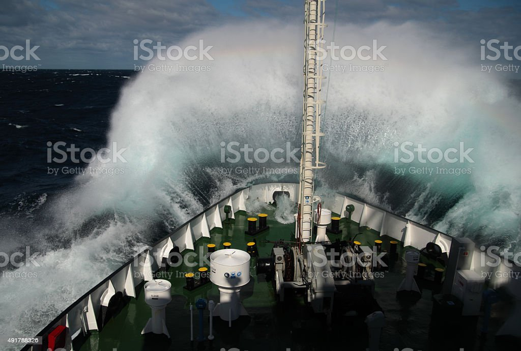 Big wave rolling over snout of the ship stock photo