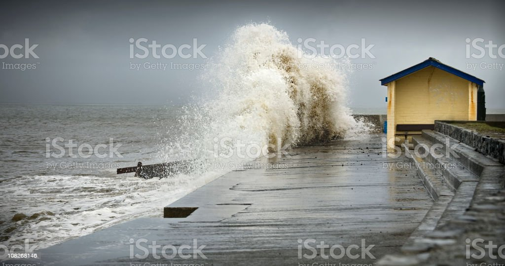 A big wave smashing into a dock in a storm stock photo