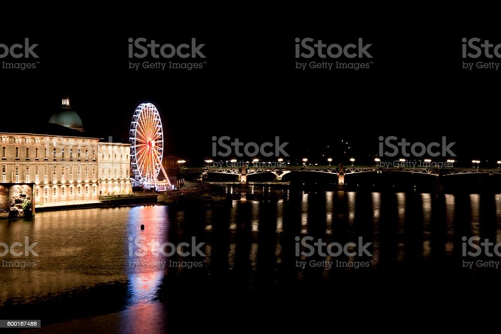 Big wheel and Saint Pierre bridge at night in Toulouse stock photo