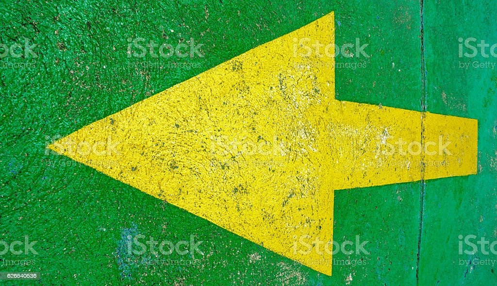 Big yellow arrow pointing to the left with green background stock photo