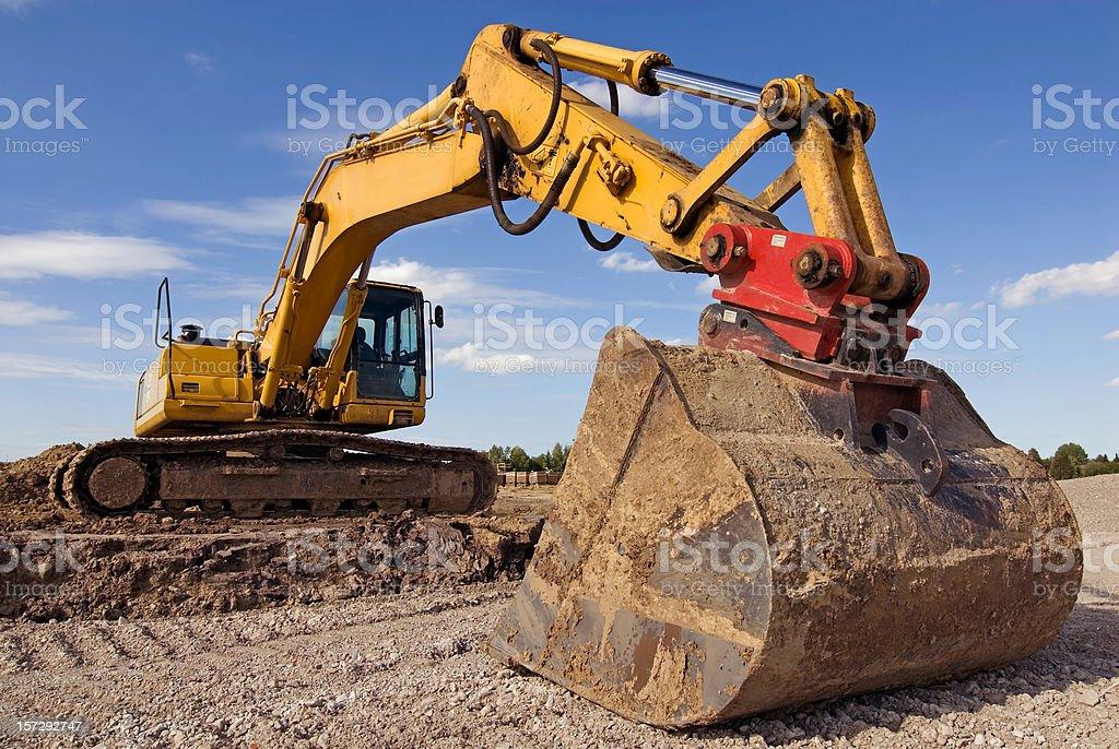 Big yellow excavator working on dirt royalty-free stock photo