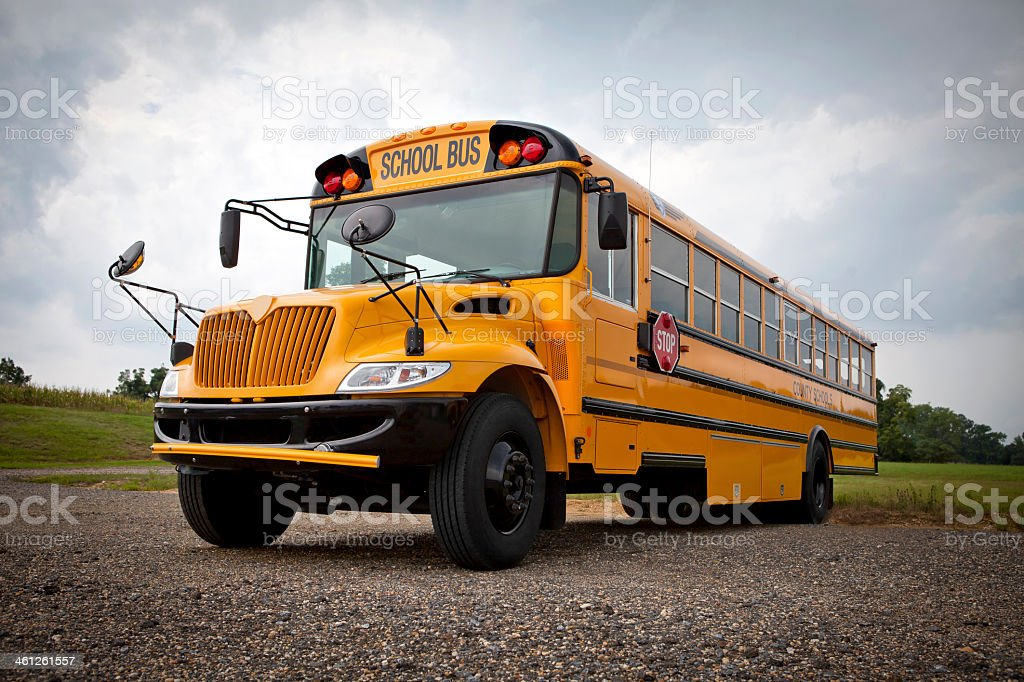 Big yellow school parked on a gravel road stock photo