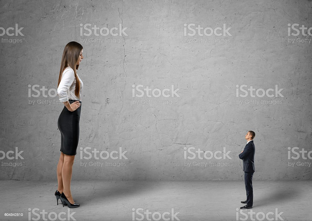 Big young businesswoman standing in front of small businessman stock photo