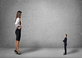 Big young businesswoman standing in front of small businessman
