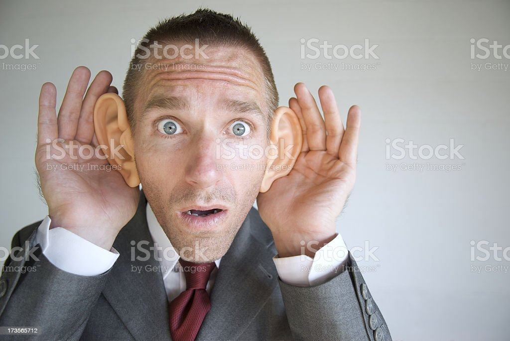 Big-Eared Businessman Listening with Funny Face Cupping Ears stock photo