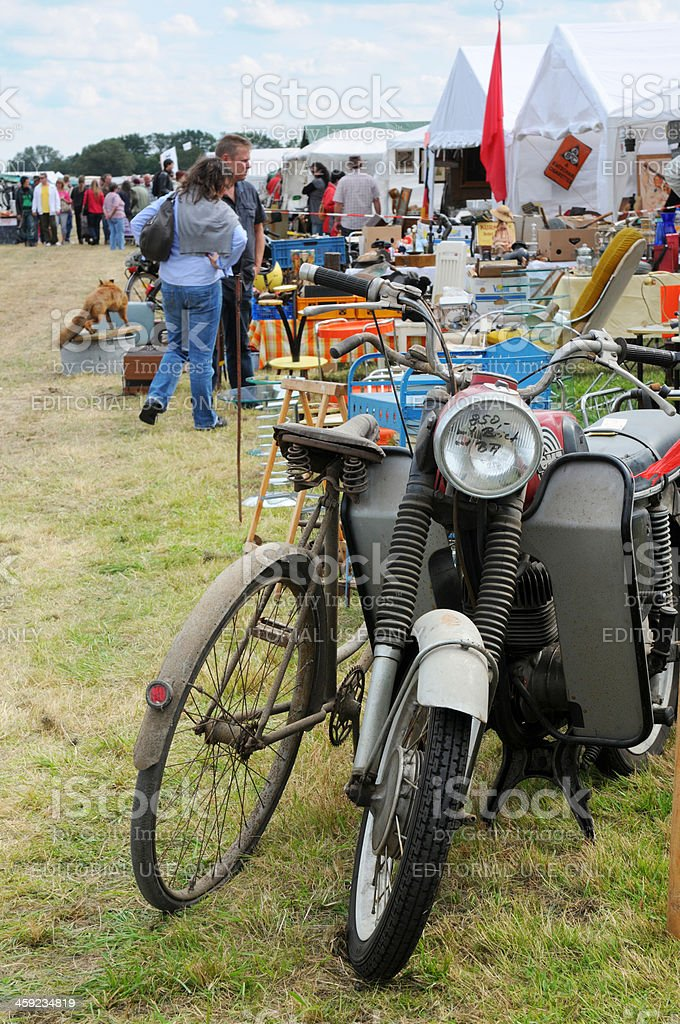 bike and motorcycle on flea market with visitors in background stock photo