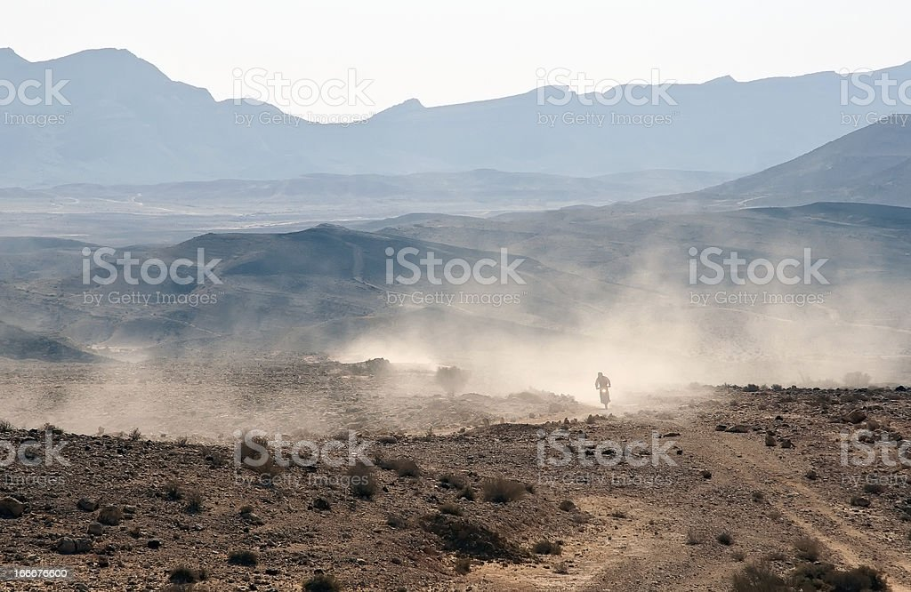 Bike crossing a stone desert. stock photo