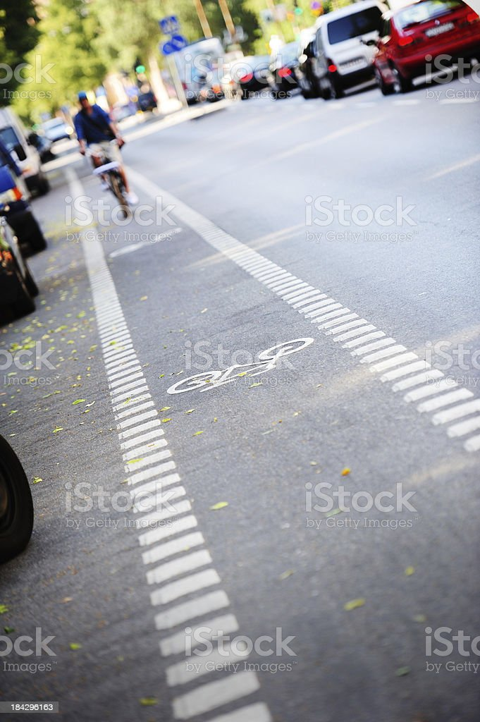 Bike lane and its symbol, bicyclist in background royalty-free stock photo