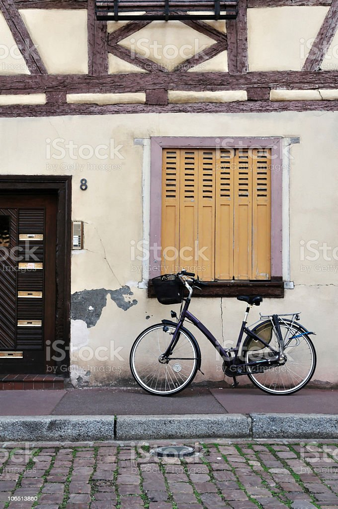 Bike parked in front of a rustic house royalty-free stock photo