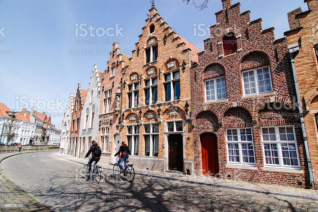 Bike pass Bruges houses, leafless tree's shadow stock photo