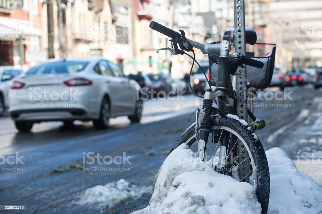 bike resting against pole in snow stock photo
