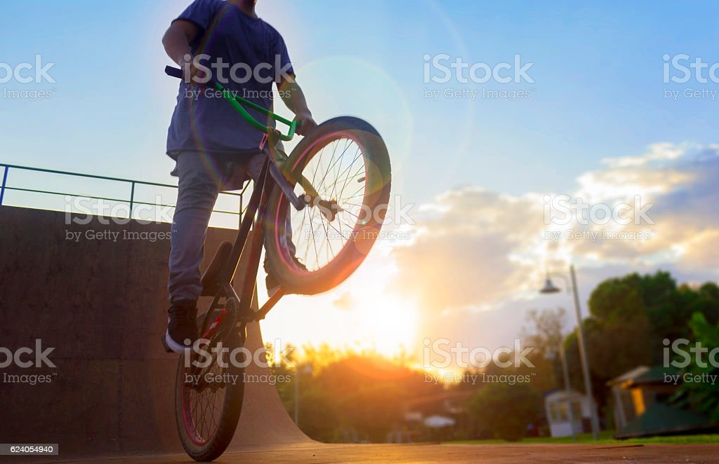 BMX bike rider jumping with bike on bicycle ramp stock photo