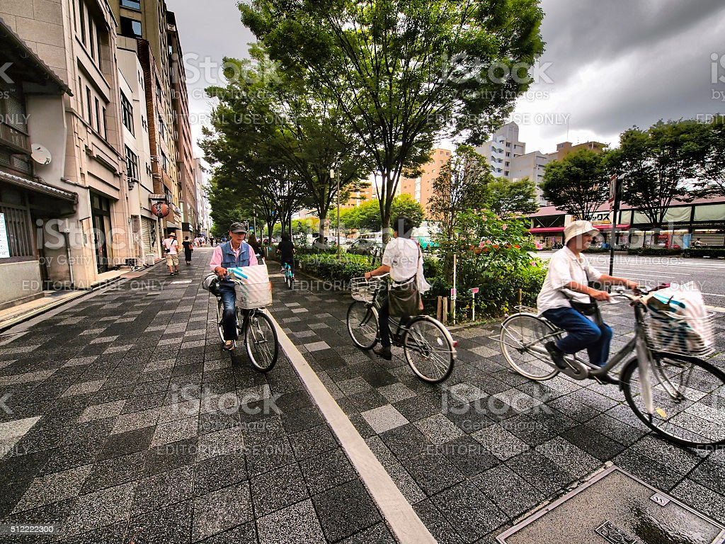 Bike riders on pavement in Kyoto, Japan stock photo