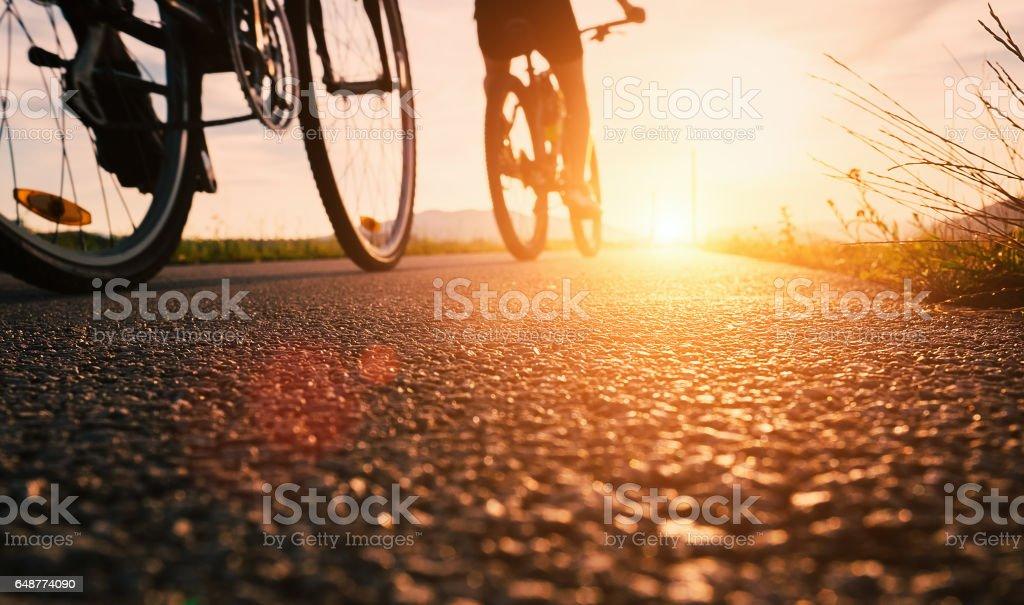 Bike wheels close up image on asphalt sunset road stock photo