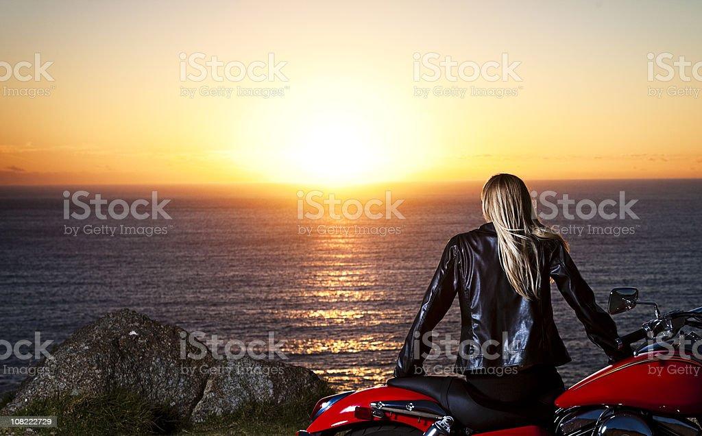 Biker babe watching sunset royalty-free stock photo