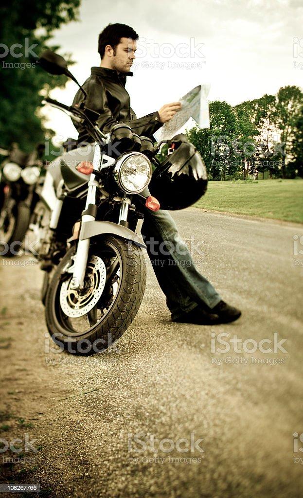 Biker checking map royalty-free stock photo