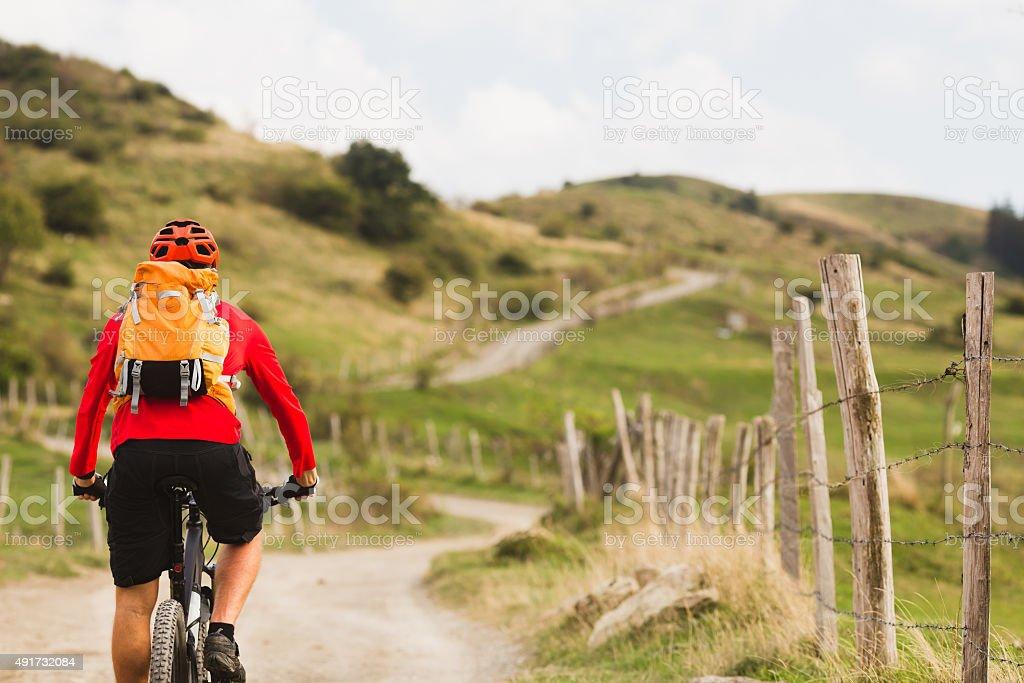 Biker cycling in beautiful mountains stock photo