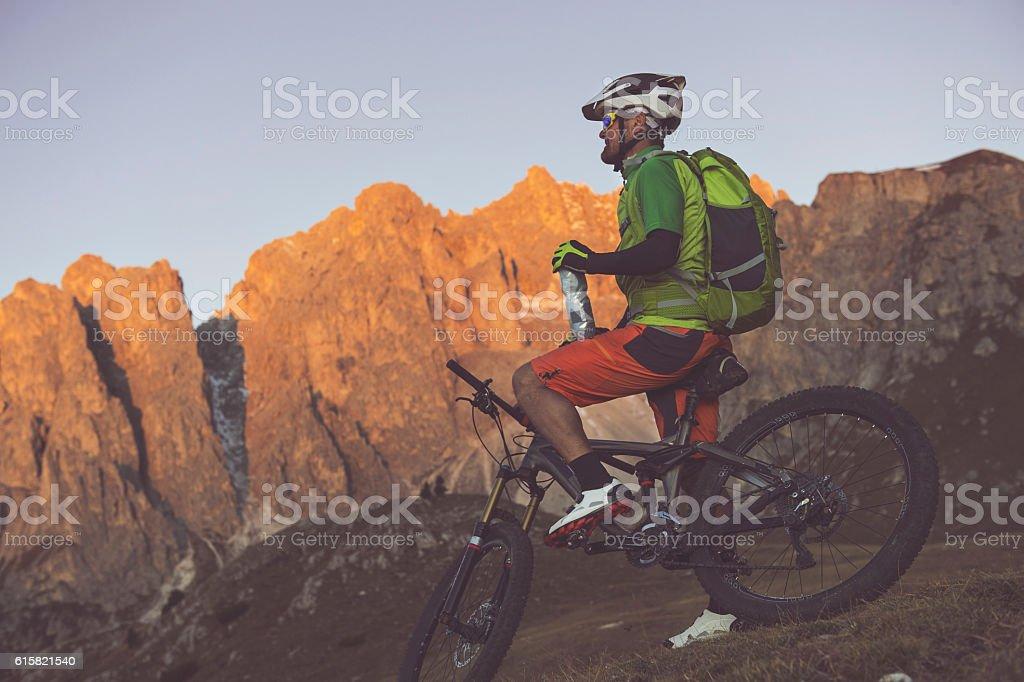 Biker drinking and enjoying the dolomites stock photo