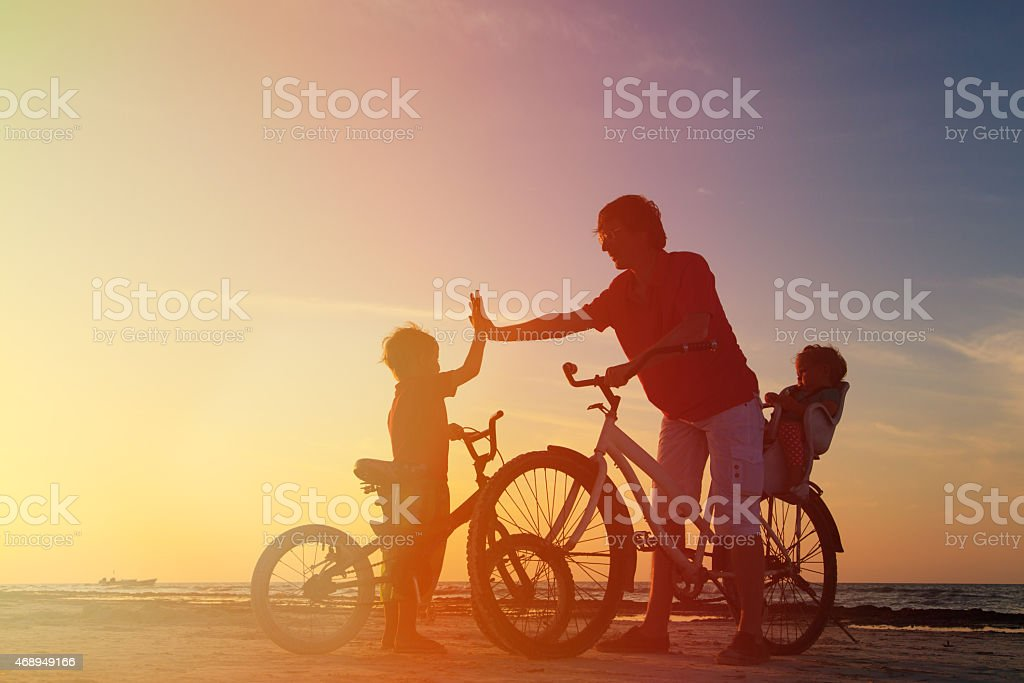 Biker family silhouette, father with two kids on bikes stock photo