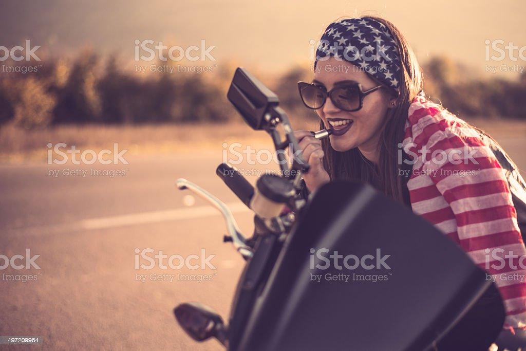 Biker girl fixes her makeup stock photo