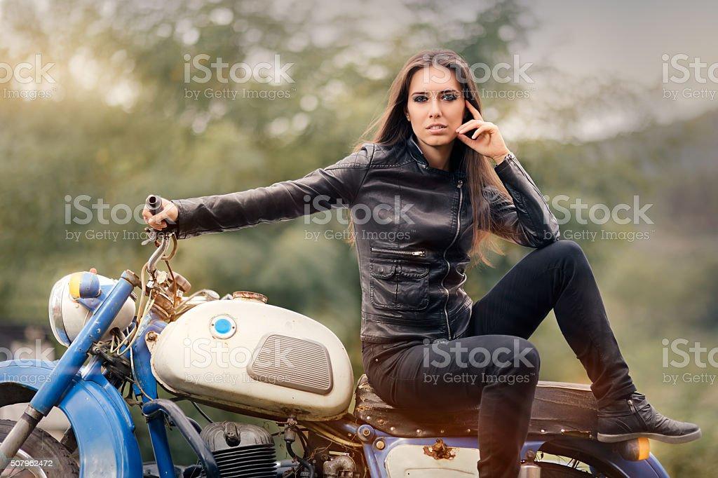 Biker Girl in Leather Jacket on Retro Motorcycle stock photo