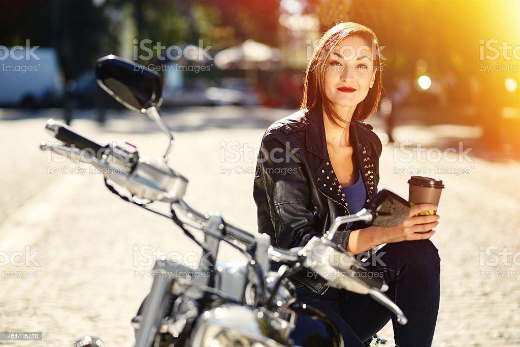 Девушка-байкер на мотоцикл, пьющий кофе Стоковые фото Стоковая фотография