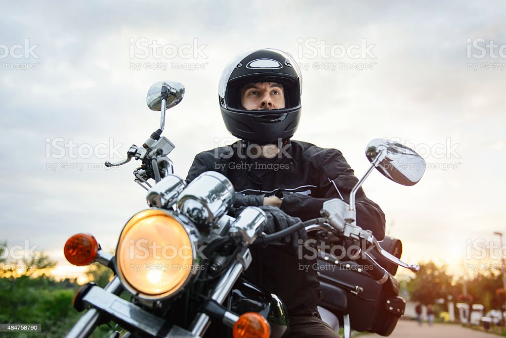 Biker in helmet driving motorcycle on sunset. stock photo