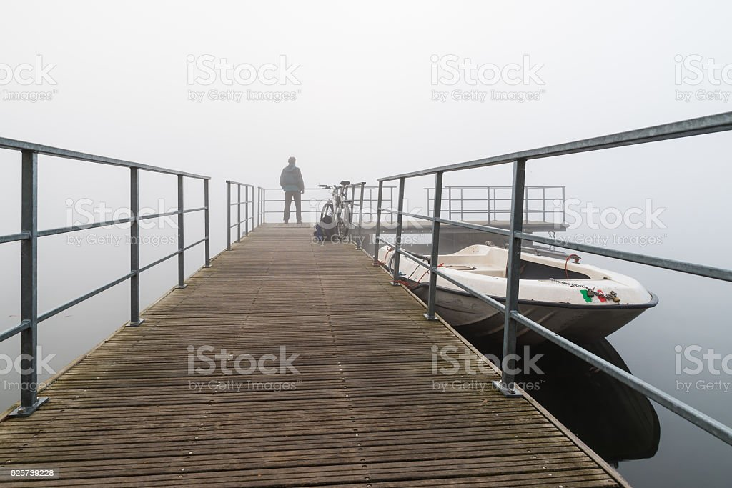 Biker in the fog on Varese lake, Biandronno Italy stock photo