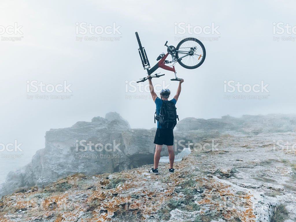 Biker lifting up his bike on top of the cliff stock photo