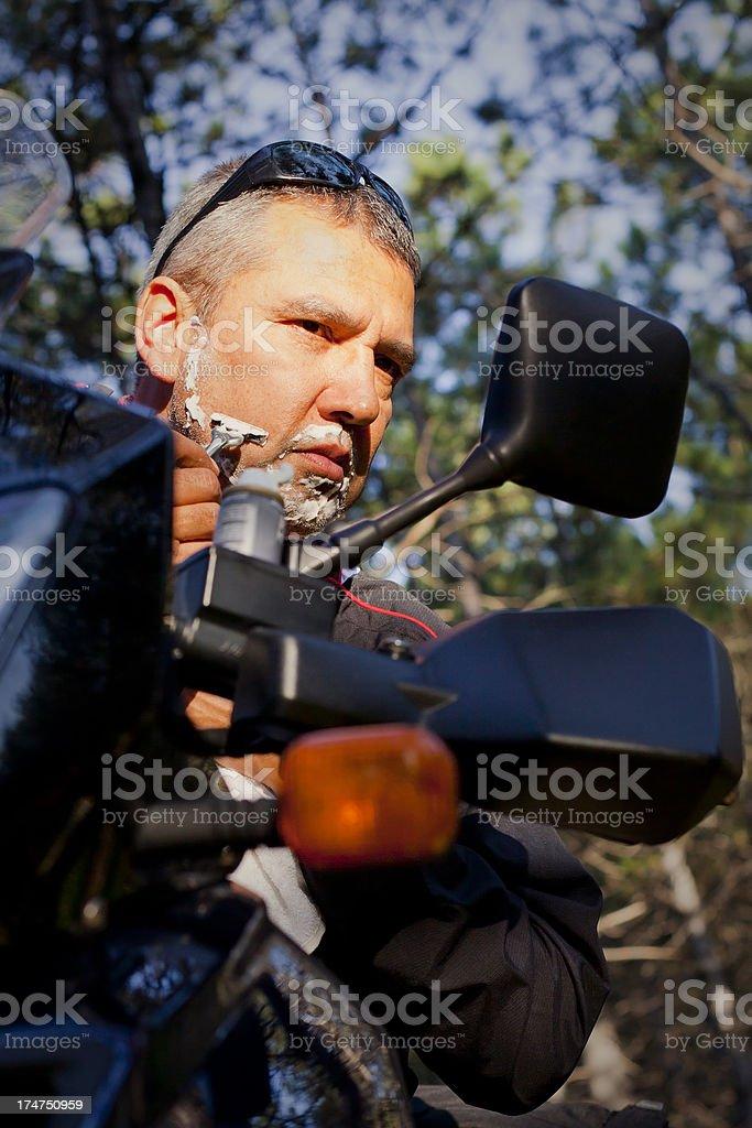 Biker Man Shaving With Razor on Motorcycle's Mirror royalty-free stock photo
