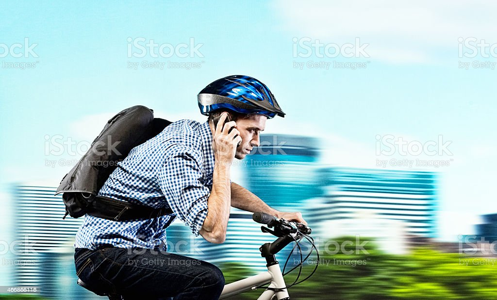Biker on mobile and riding bicycle outdoors stock photo