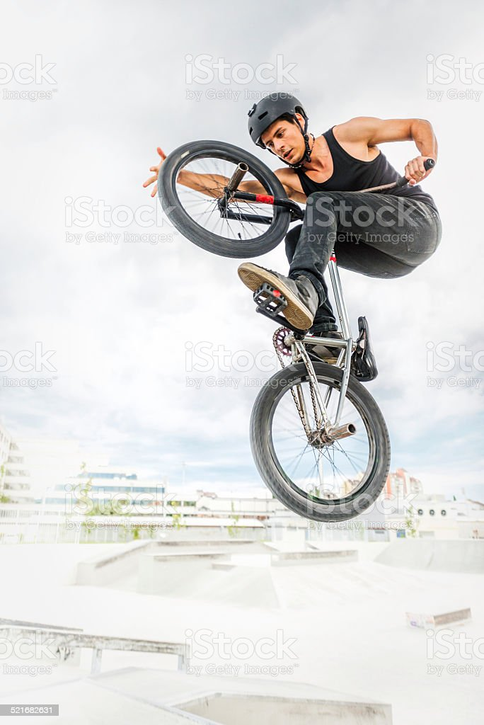 BMX biker performing a stunt in ramp park.