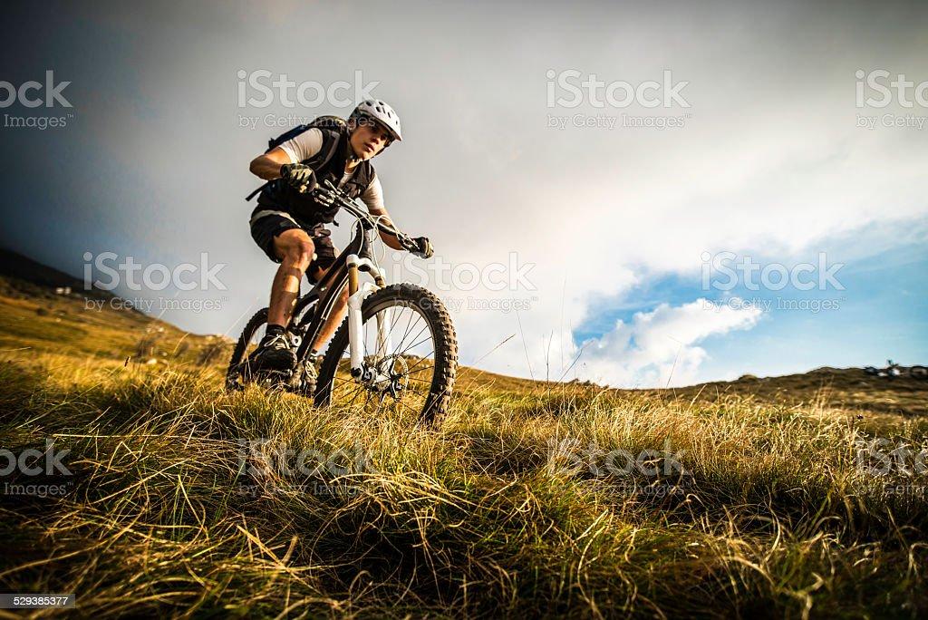 Biker Riding on a Mountain Trail stock photo