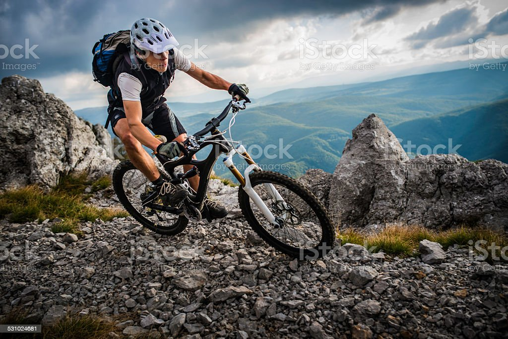 Biker Riding on a Mountain Trail stock photo