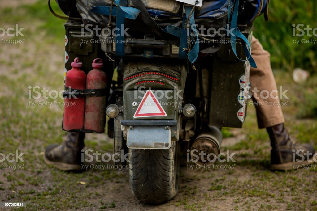Biker sitting on motorcycle on an empty road, close-up view on rear wheel. View from land. Transportation concept. A motorbike stock photo