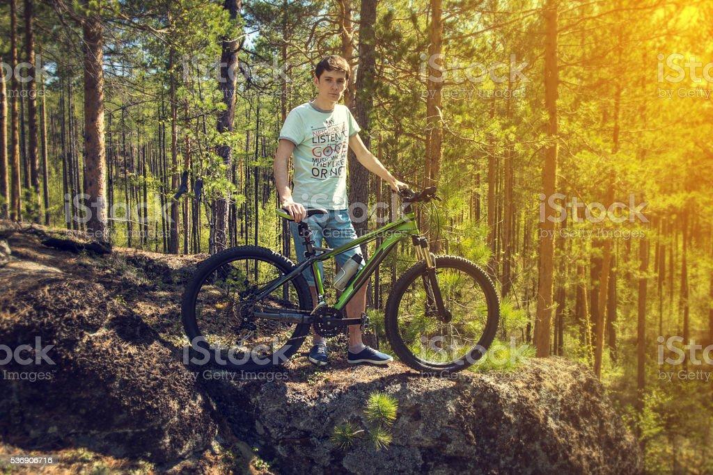 biker with bike on the rocks. Sport, adventure, motivation. stock photo