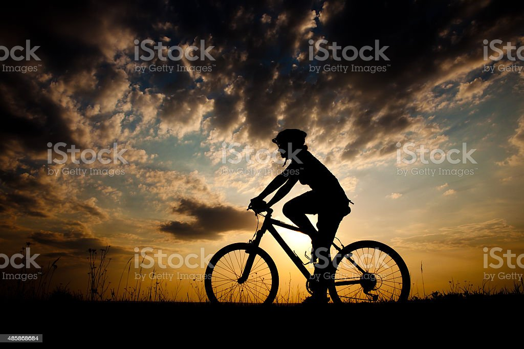 Biker-girl at the sunset on the meadow stock photo