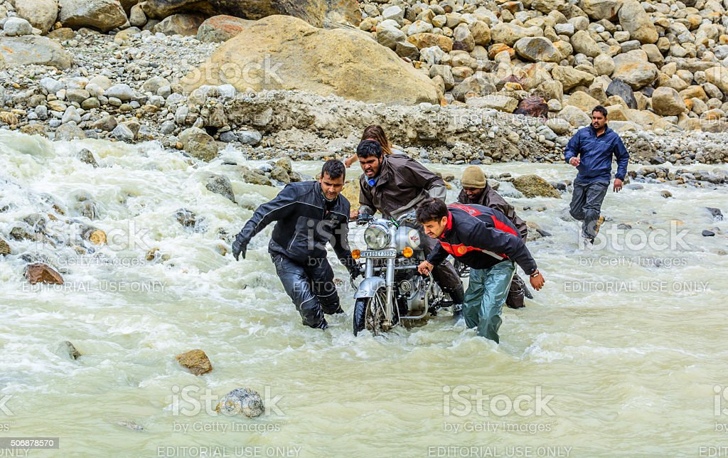 Bikers helping each other to cross through glacial waterfall stock photo