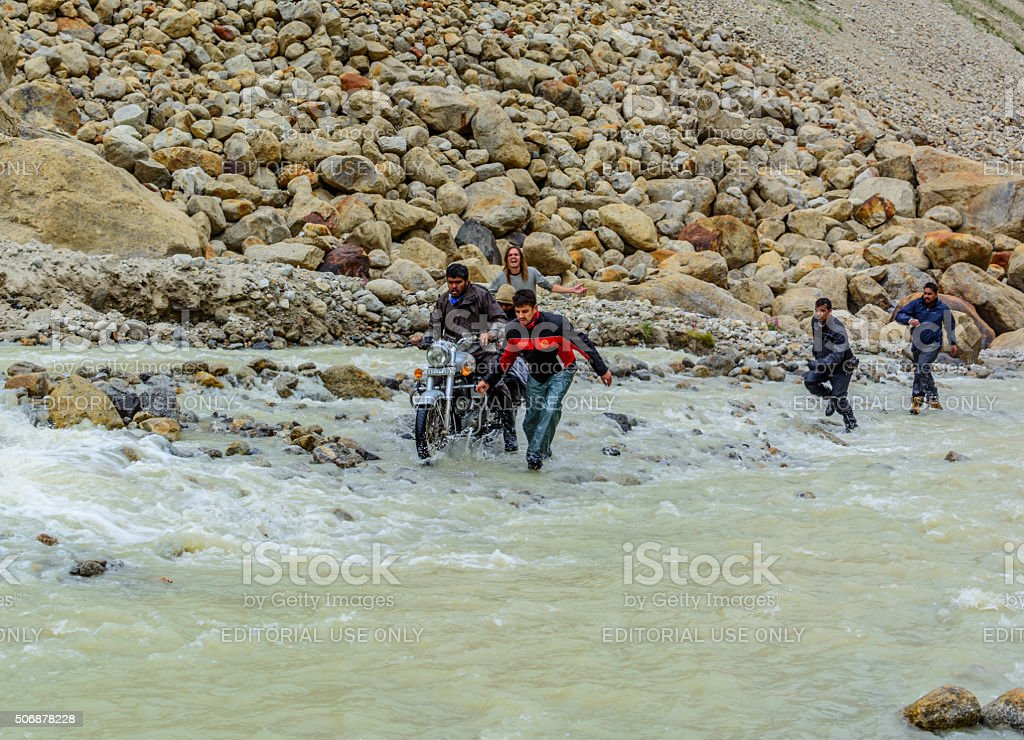 Bikers helping each other to cross through waterfall on road stock photo