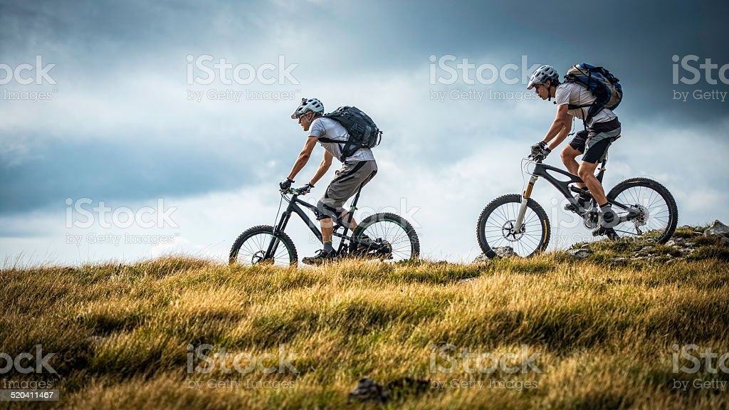 Bikers Riding On A Mountain Trail stock photo