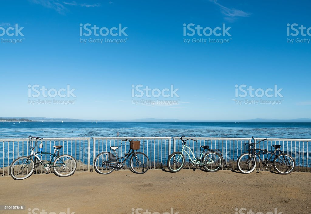 Bikes are standing by the ocean boardwalk in Santa Cruz stock photo