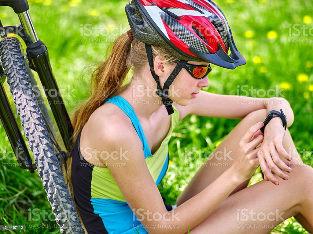 Bikes cycling girl. Bicyclist looks on smart watch. stock photo