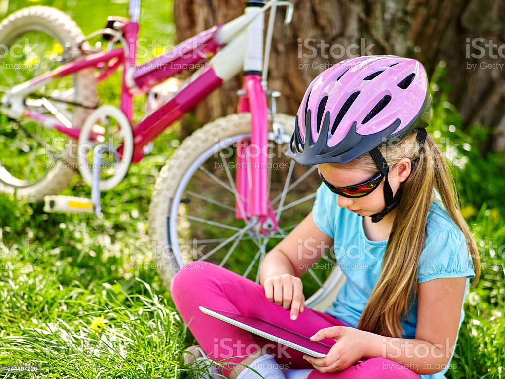 Bikes cycling girl wearing helmet watching at tablet pc . stock photo