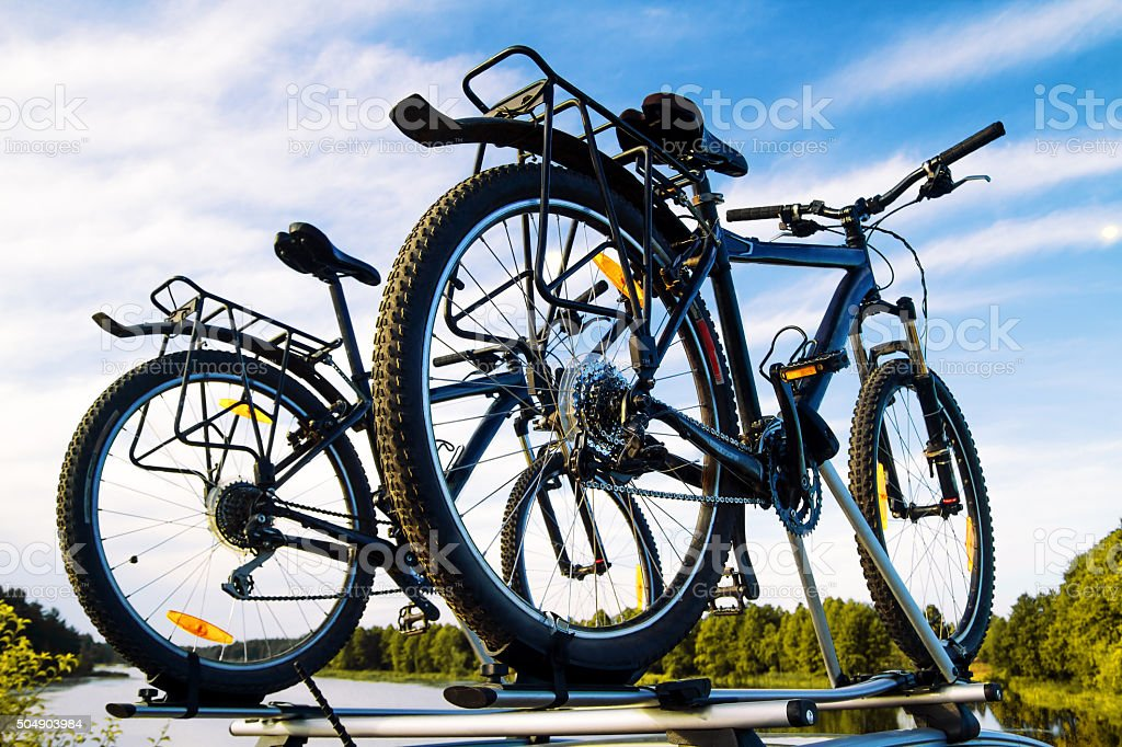 Bikes on top of a car against the sky. stock photo