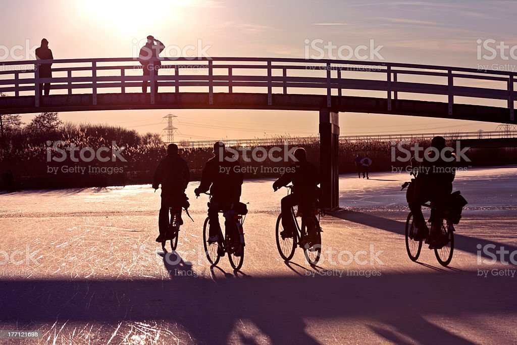 Biking on a frozen canal in winter at sunset royalty-free stock photo