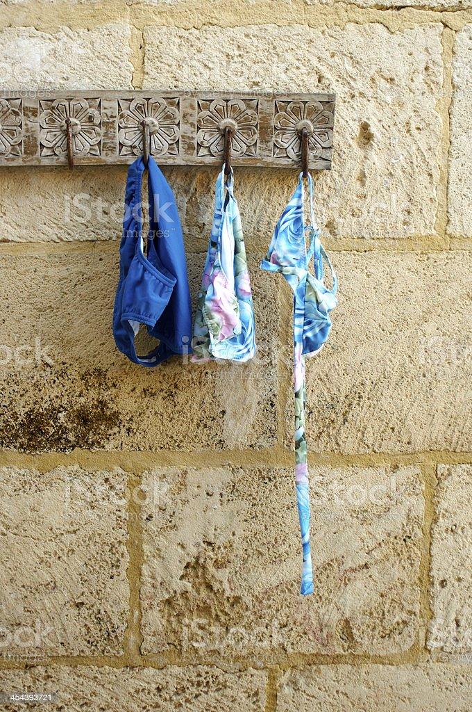 Bikini and Swimming Trunks Hanging on Hook stock photo
