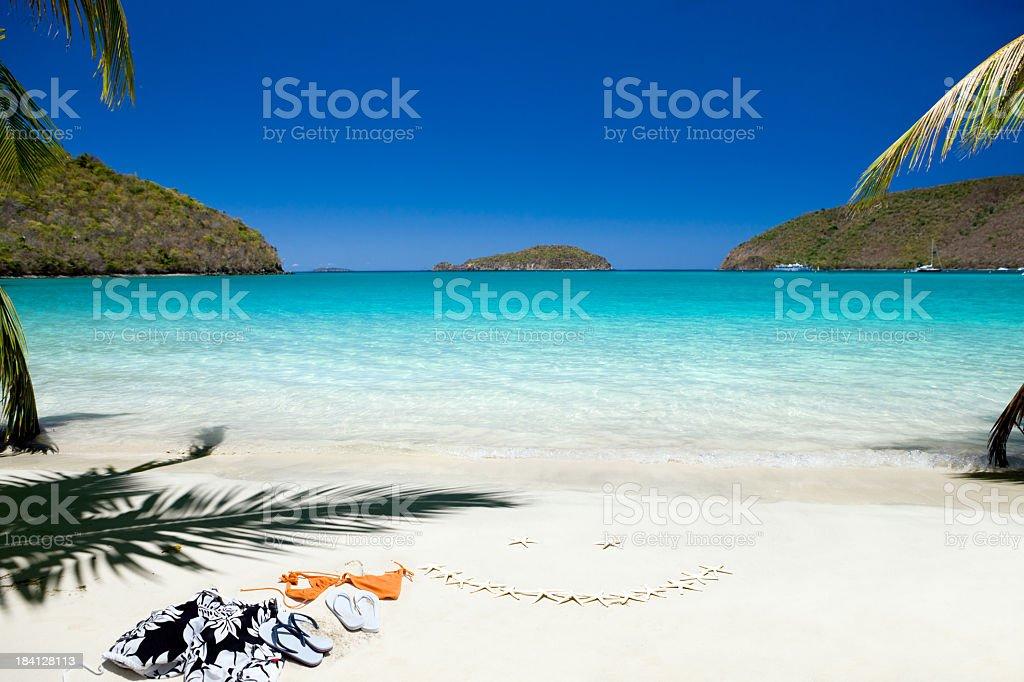 bikini and swimtrunks left on beach next to smiley face stock photo