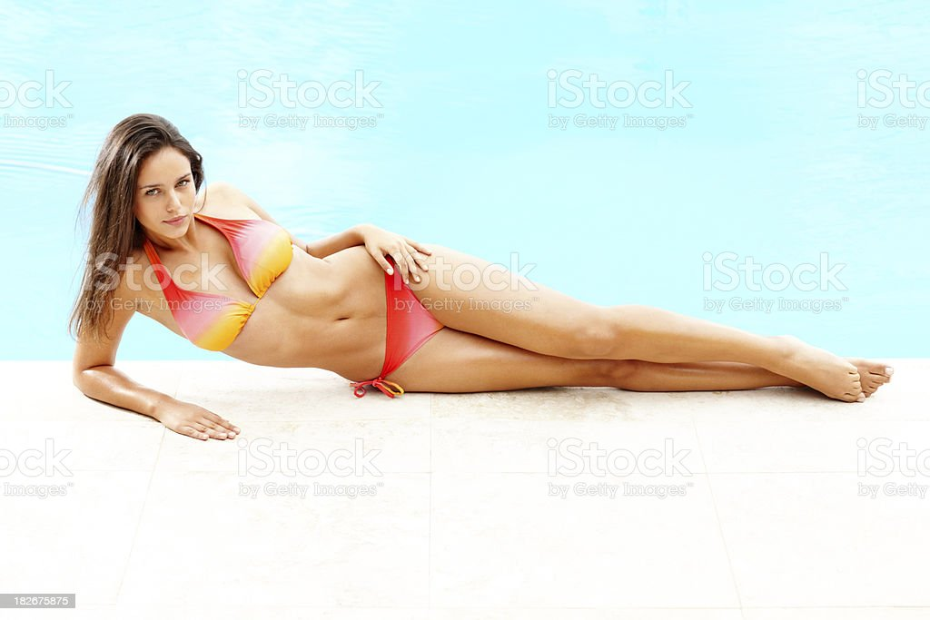 Bikini female lying seductively by a swimming pool stock photo